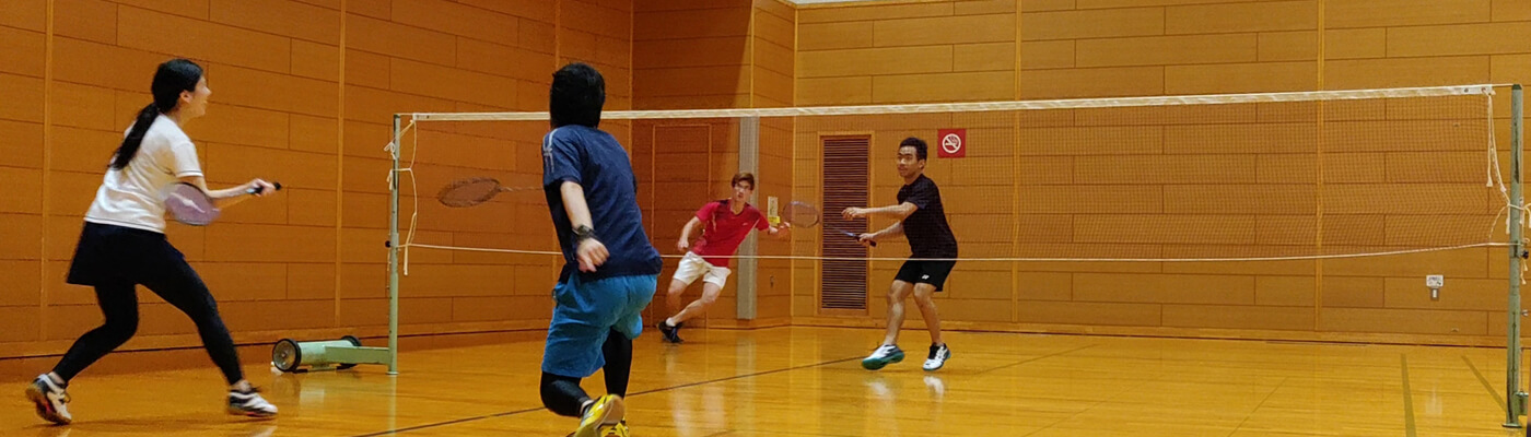 four people playing badminton